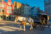 image of four-wheel  - White horse hitched to a four wheel horse carriage waiting for tourists on Grote Markt square of Brugge Christmas - JPG