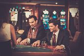 image of roulette table  - Two fashionable men in suits behind table in a casino - JPG