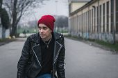stock photo of anarchists  - Punk guy with beanie posing in the city streets - JPG