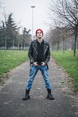 stock photo of anarchists  - Punk guy with beanie posing in a city park - JPG