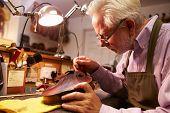 stock photo of violin  - Man Restoring Violin In Workshop - JPG