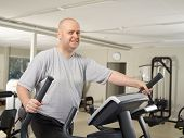 pic of elliptical  - Mature man takes care of his health and he use elliptical trainer in the gym - JPG