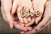 picture of word charity  - two pairs of hands holding word love - JPG