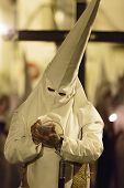 picture of conic  - Religious Catholic penitent dressed in a conical hat and robes standing writing notes during the Holy Week procession in Seville Spain - JPG
