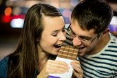 image of love bite  - Young couple eat together chocolate on date  - JPG