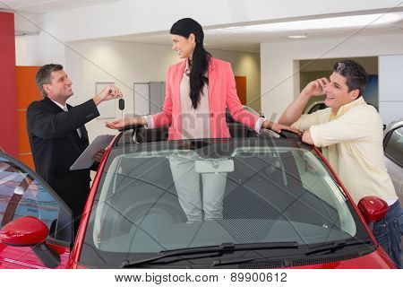 Cheerful woman standing in red cabriolet at new car showroom