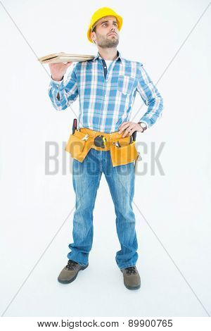 Full length of thoughtful worker carrying wooden planks over white background