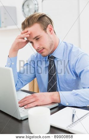 Tired businessman using his laptop in his office