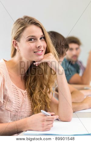 Portrait of smiling female student writing notes in classroom