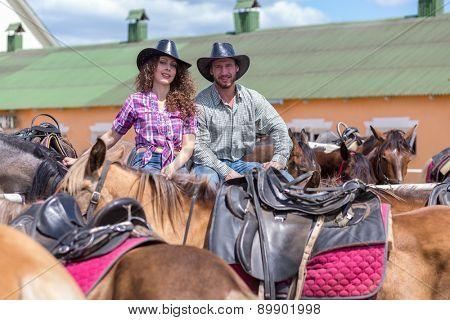cowboy couple smiling among horses
