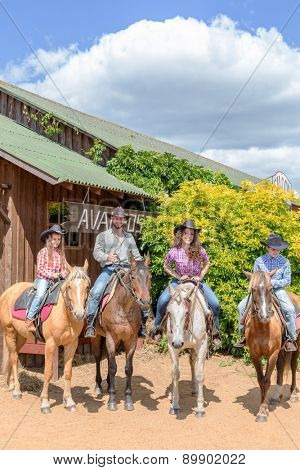 cowboy family of four on horses on background of wooden building