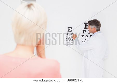 Blonde woman doing eye exam in medical office