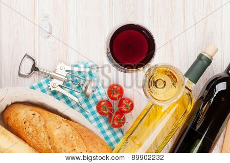 White and red wine, cheese and bread on white wooden table background. Top view