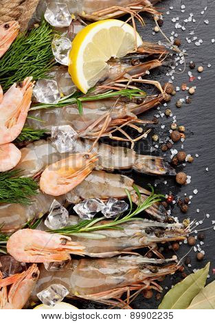 Fresh prawns with spices on black stone background. Top view
