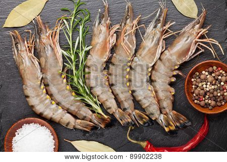 Fresh raw tiger prawns and spices on black stone plate. Top view