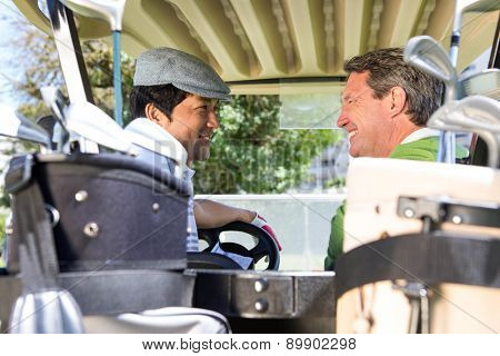 Golfing friends driving in their golf buggy smiling to each other at golf course
