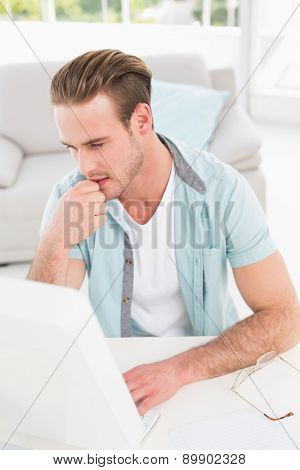 Concentrated businessman typing on keyboard in his office