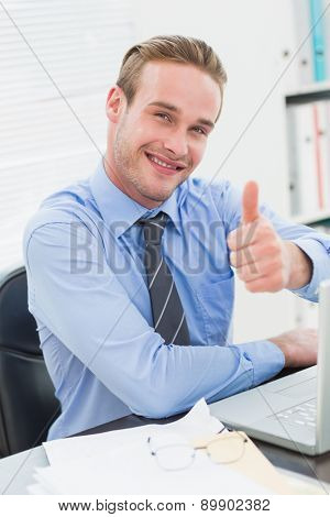 Smiling businessman sitting with thumb up in his office
