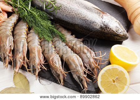 Fresh raw sea food with spices on black stone plate. Top view