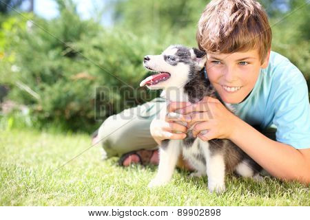 Happy boy sitting on the grass with puppy husky