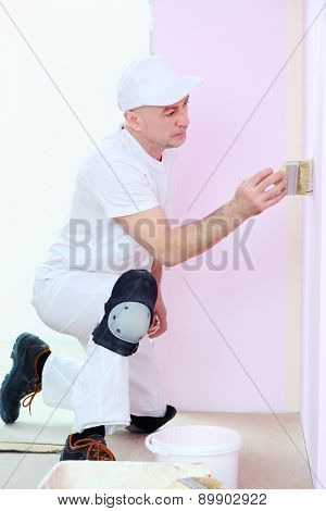 Finisher in white clothes with a brush in hand painted walls in pink room