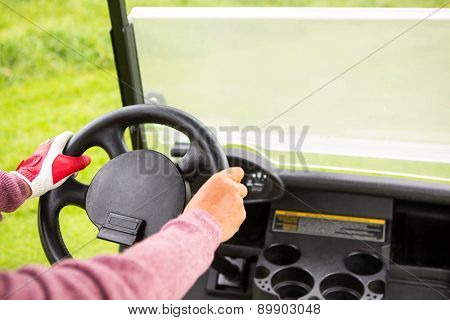 Golfer driving his golf buggy forward at the golf course