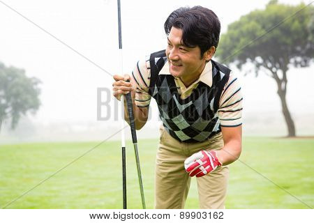 Golfer holding golf ball and club at the golf course