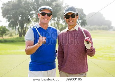 Golfing friends smiling at camera holding clubs at the golf course
