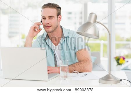 Focused businessman on the phone while using laptop in his office