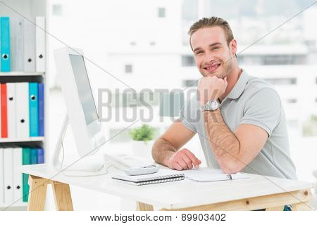 Smiling businessman sitting at his desk in his office