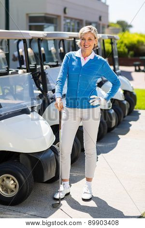 Female golfer beside golf buggy at the golf course parking