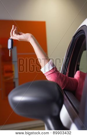 Womans hand holding car key at new car showroom