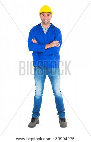 Full length portrait of happy manual worker standing arms crossed on white background