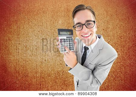 Geeky smiling businessman showing calculator against weathered surface