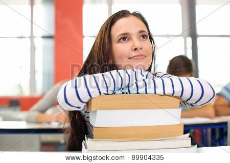 Thoughtful female student with books in the classroom