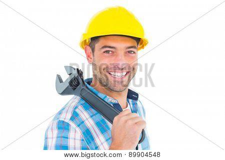Portrait of smiling manual worker holding adjustable spanner on white background