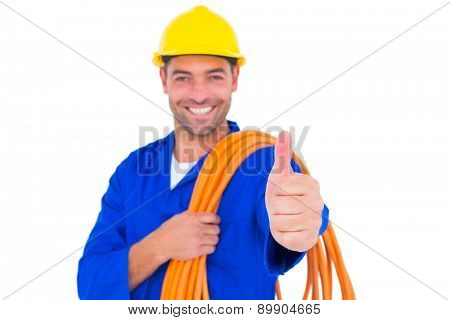 Portrait of happy electrician with rolled wire gesturing thumbs up on white background
