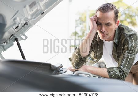Upset man checking his car engine after breaking down in a car park