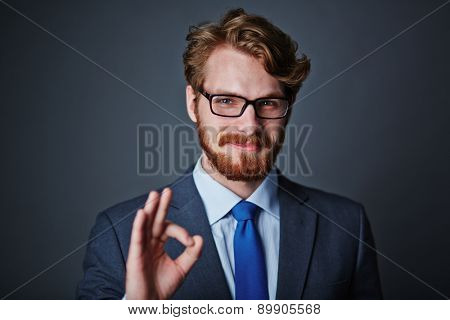 Confident businessman in eyeglasses showing okay sign