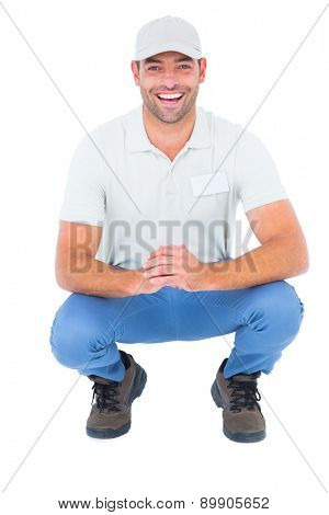 Portrait of cheerful handyman crouching on white background