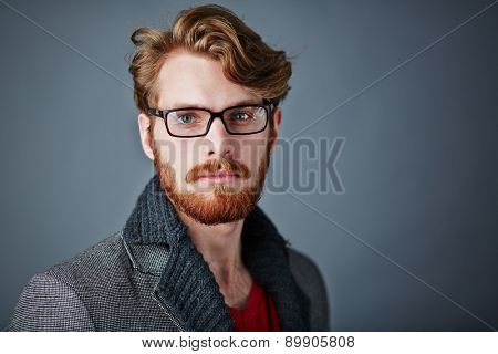 Bearded man in smart casualwear and eyeglasses looking at camera