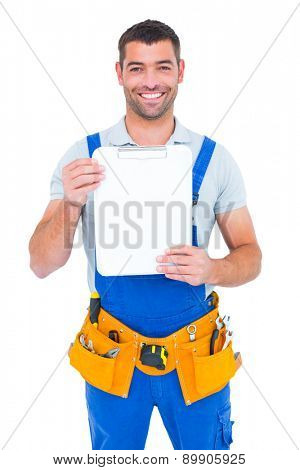 Portrait of happy repairman showing blank clipboard on white background