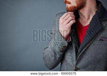 Pensive young man in smart casualwear touching his beard