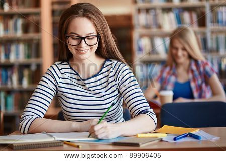 Happy girl in eyeglasses making notes at lesson