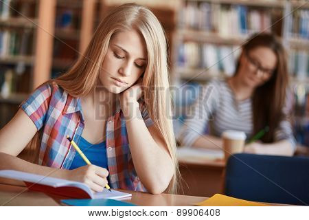Serious girl making notes at lesson in college