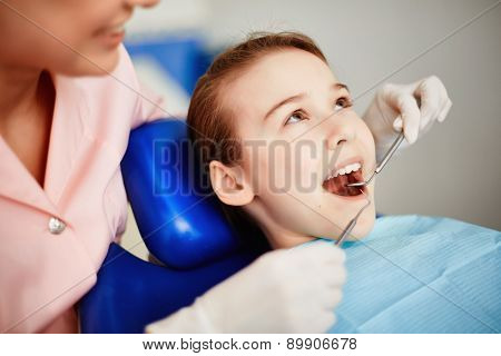 Pretty child with open mouth during oral checkup