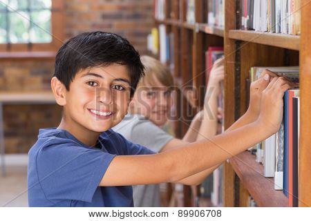 Cute pupils looking for books in library at the elementary school