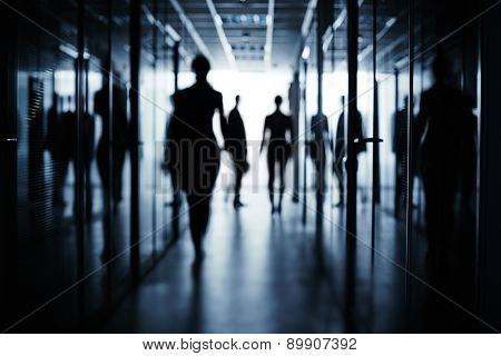 Silhouettes of several business people in corridor of office building