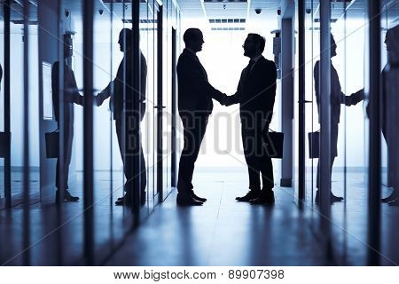 Silhouettes of two businessmen handshaking in corridor of office building