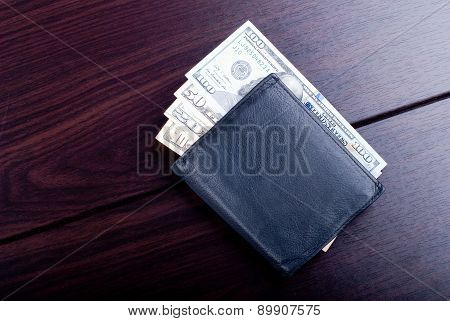 Several Dollar Bills In A Black Wallet On A Burgundy Table, Top View